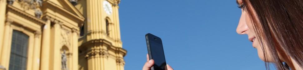 Eine Frau nutzt ihr Handy um mit einer Sehenswürdigkeit zu interagieren (macht Fotos, scannt einen QR code ein, etc.)